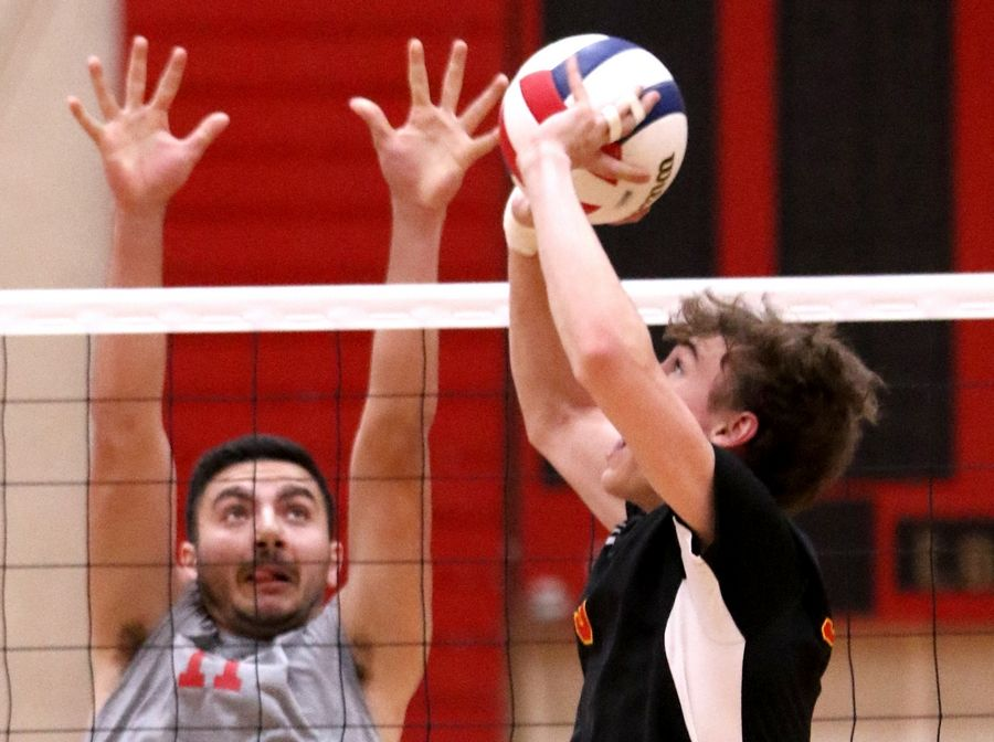 Schaumburg's Ryan Luecht, right, passes the ball as Barrington's Ricky Gibson defends during varsity boys volleyball in Schaumburg on Thursday.