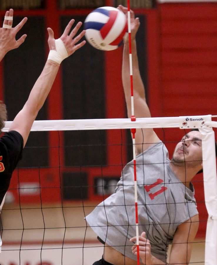Barrington's Ricky Gibson slams the ball over the net during varsity boys volleyball in Schaumburg on Thursday.