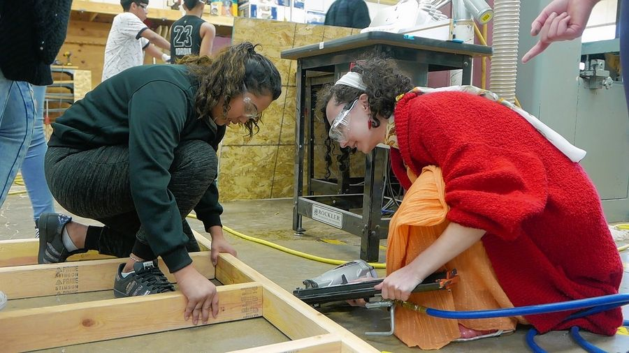 Rolling Meadows High School junior Estefani Mejia, from left, helps Hersey High School senior Zoe Axelrod put together the frame of a tiny house intended for a homeless veteran.