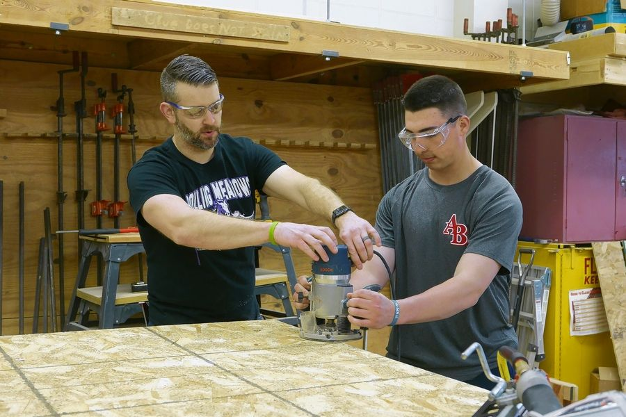 Rolling Meadows High School math teacher Brett Olson, left, works with Hersey High School senior Jake Irwin during the construction of walls and roofs for tiny homes on Friday.