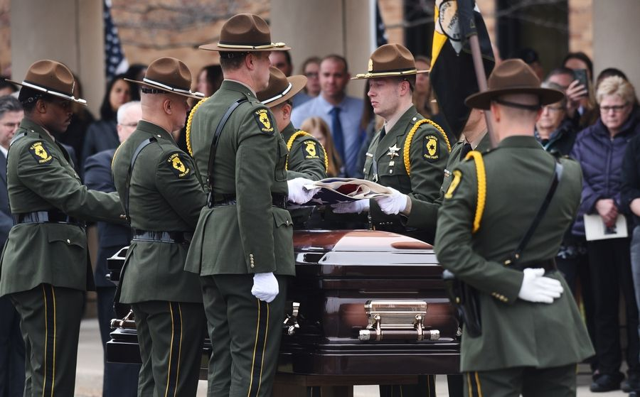 Honor Guard pallbearers prepare to fold the flag from the casket of Illinois State Police trooper Gerald Ellis during his funeral at the College of Lake County in Grayslake.