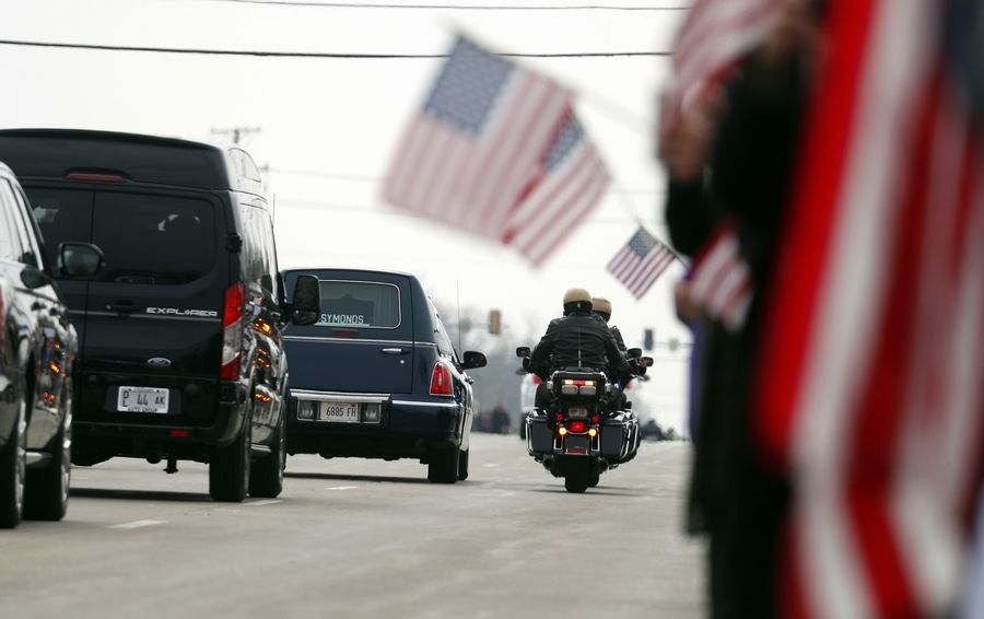 The hearse carrying the body of Illinois State trooper Gerald Ellis passes the Lake County Farm Bureau in Grayslake during his funeral procession Friday.