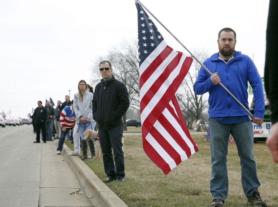Ryan Curtis of McHenry holds a flag as the funeral procession for Illinois State Police trooper Gerald Ellis leaves the College of Lake County in Grayslake, where services were held Friday.