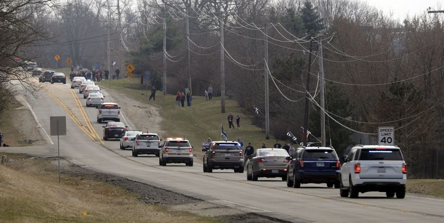 The funeral procession for of Illinois State Trooper Gerald Ellis heads down Deep Lake Road in Lake Villa as they head to the cemetery Friday.