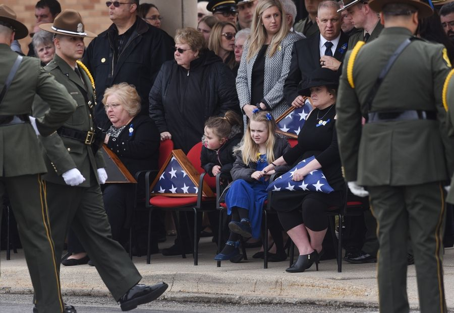 Stacy Ellis, wife of the Illinois State Police trooper Gerald Ellis, and daughters Kaylee, middle, and Zoe, view the ceremony taking place during his funeral Friday at the College of Lake County in Grayslake.