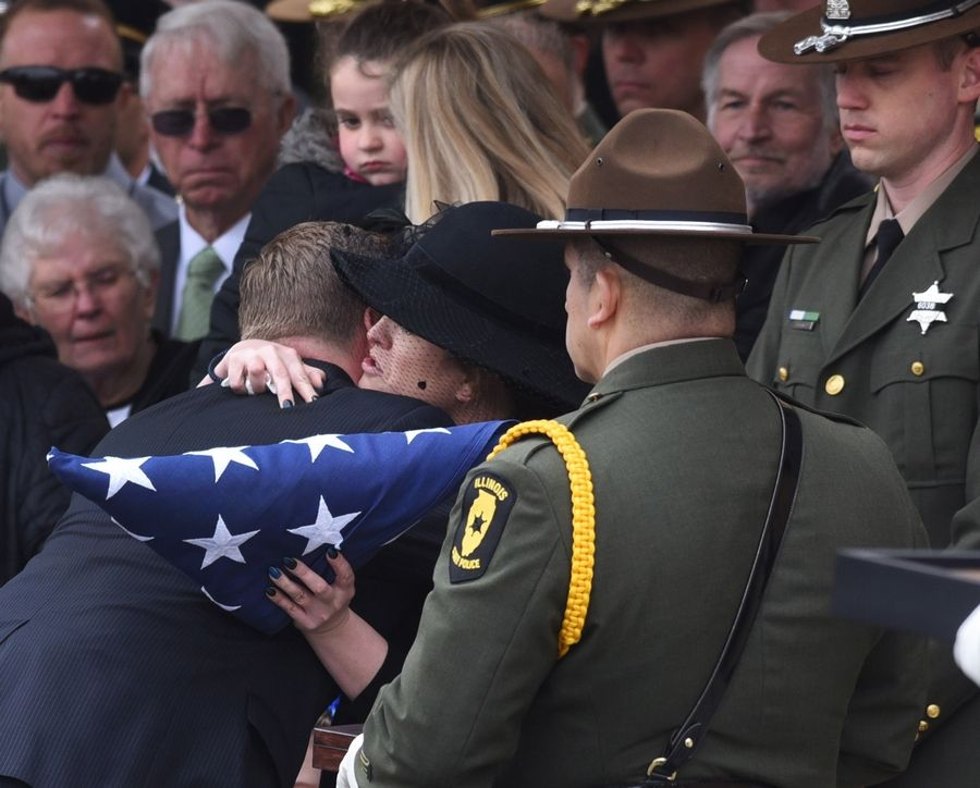 Stacy Ellis hugs Acting Director of the Illinois State Police Brendan Kelly after receiving the folded flag from the casket during the funeral for her husband, Illinois State Police trooper Gerald Ellis.