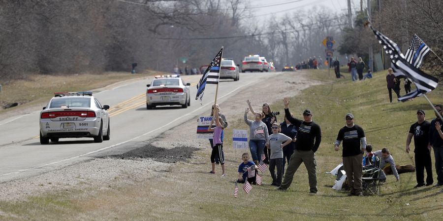 People wave flags as a funeral procession for of Illinois State Trooper Gerald Ellis heads down Deep Lake Road in Lake Villa as they head to the cemetery Friday.