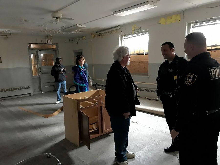 """I'm just flooded with memories,"" said Michael Mayer of Huntley, center, an employee of the former Larkin Center in Elgin. Here he is pictured talking to Elgin police officers Kevin Snow, second from right, and Bob Engelke, far right, during a tour of the building Friday morning."