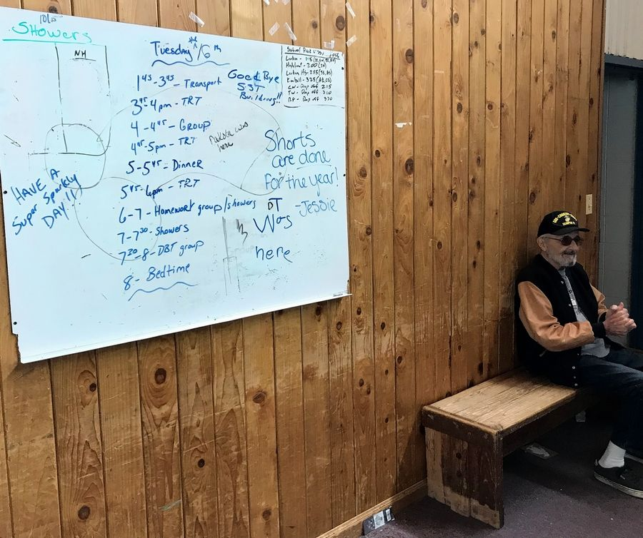 "Bob Hoffman of Elgin worked at the Larkin Center for about 17 years until the mid-1990s. He's pictured here in a former dormitory building where a dry erase board still displays a daily schedule. ""It seems weird,"" he said. ""It seems smaller than what it was like."""