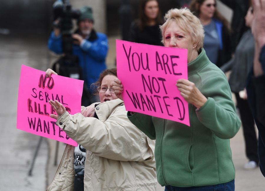 Aurora-area residents Mary Finlayson, left, and Mary Alm protest Friday outside Wayside Cross Ministries.