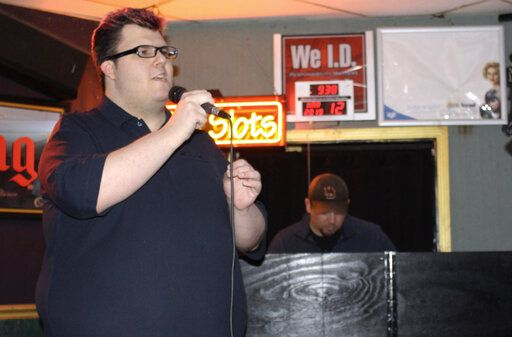 "Nathan Elmore, 26, of Belleville, sings ""Mamma Mia,"" one of his favorite songs, on karaoke night at Schatze's Bar and Grill on March 6, 2018 in Belleville, Ill.  The 26-year-old reached the goal  of his 1,000 karaoke songs, when he got up on stage and sang the Christina Perri hit ""A Thousand Years.� It was a big accomplishment for someone who was painfully shy as a child and faced plenty of challenges in school.  (Teri Maddox/Belleville News-Democrat via AP)"