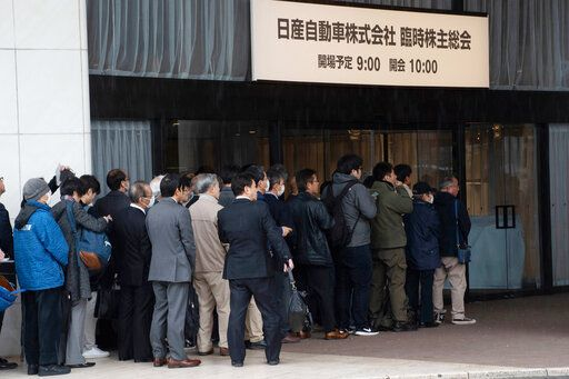 "In this photo released by Nissan Motor Co., Nissan shareholders wait to enter the venue for a meeting in Tokyo Monday, April 8, 2019. Nissan shareholders approved on Monday the ouster from the Japanese automaker's board former Chairman Carlos Ghosn, who faces allegations of financial misconduct. The signs reads "" Nissan Motor Corporation shareholders' meeting."" (Nissan Motor Co. via AP)"