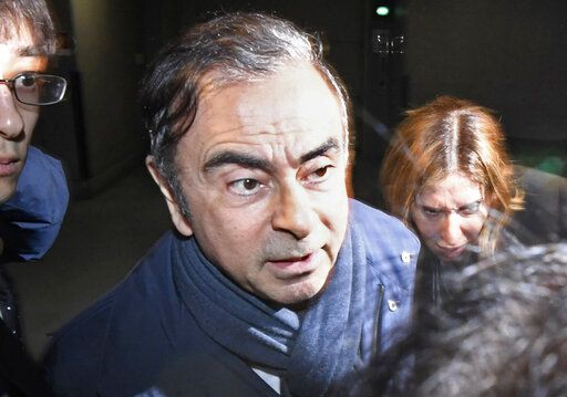 FILE - In this April 3, 2019, file photo, former Nissan Chairman Carlos Ghosn, center, leaves his lawyer's office in Tokyo. Nissan Chief Executive Hiroto Saikawa has apologized to shareholders for the unfolding scandal at the Japanese automaker and asked for their approval to oust from the board former Chairman Ghosn, who has been arrested on financial misconduct charges. Saikawa and other Nissan Motor Co. executives bowed deeply at a Tokyo hotel Monday, April 8, 2019, where the extraordinary shareholders' meeting was being held. (Sadayuki Goto/Kyodo News via AP, File)
