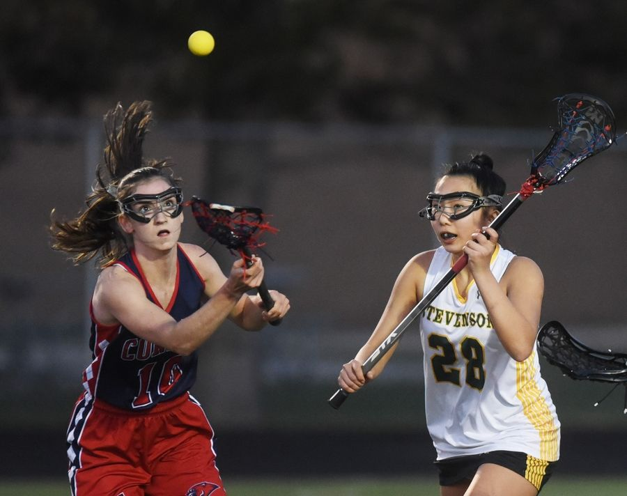 Conant's Mackenzie Lunkes, left, and Stevenson's Michelle Shen (28) eye the ball during Monday's girls lacrosse match in Lincolnshire.