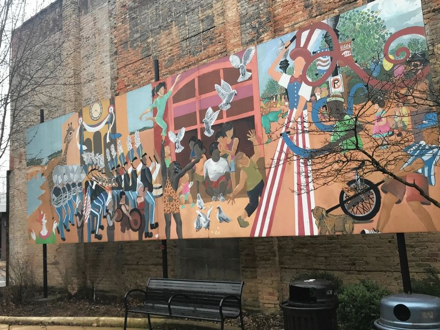 "The free-standing ""Parade Mural"" by the Outdoor Exhibition Group is on a pedestrian walkway between Spring and Grove avenues in downtown Elgin. It is owned by the city."