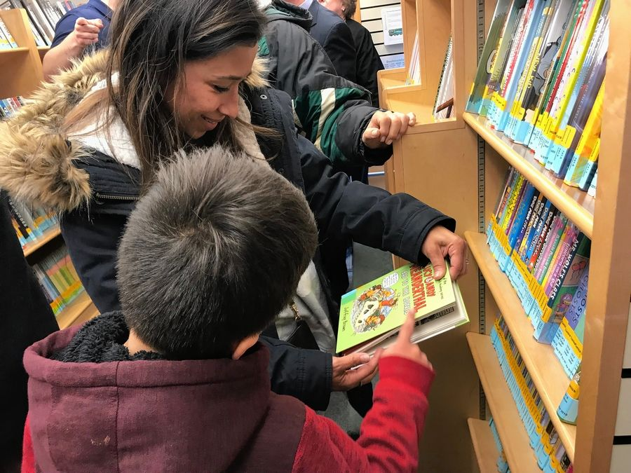 Veronica Garcia of South Elgin and her son check out the collection of the bookmobile unveiled Wednesday by the Gail Borden Public Library in Elgin.