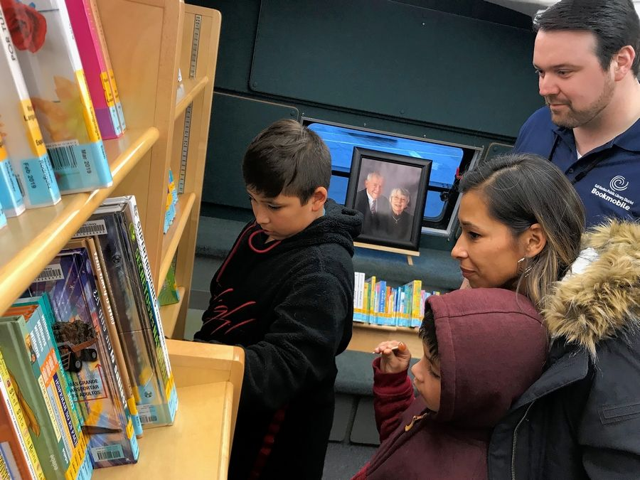 Veronica Garcia of South Elgin and her two sons check out the collection of the bookmobile unveiled Wednesday by the Gail Borden Public Library in Elgin. On the right is Danny Rice, the library's manager of bookmobile services, and in the background a photo of benefactors Jack and Marlene Shales.