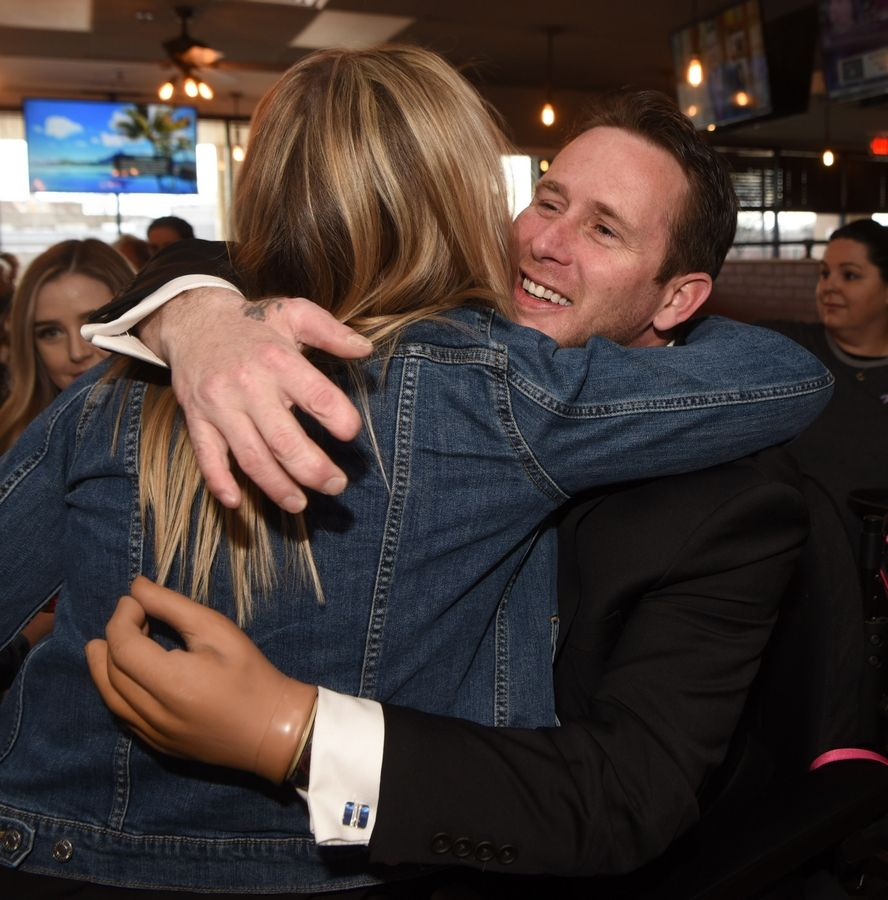 Rolling Meadows Army veteran Bryan Anderson greets Vanessa Fiscus of Fox River Grove on Tuesday before receiving the Eagle Rare Life Award from Eagle Rare Bourbon at Rep's Place in Rolling Meadows.