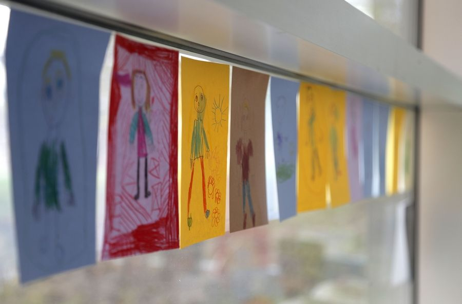 Self-portraits line the windows of the children's library at Wauconda Area Public Library. Adults and children created the drawings using crayons, colored pencils, and markers.