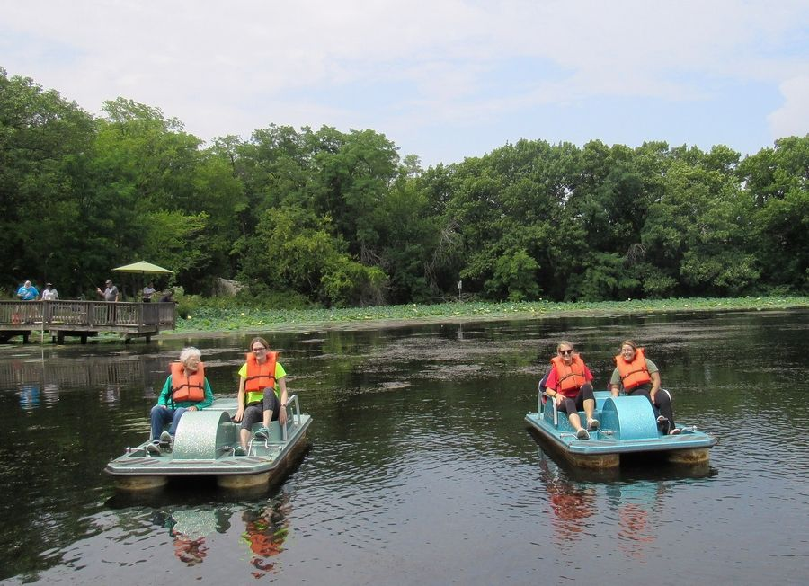 Pathway to Living residents ride paddle boats during a camping trip organized by their senior living community.