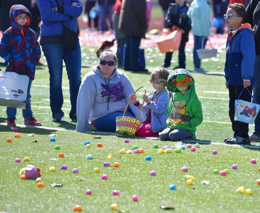 Riley Chancey, 6, wears his Ninja Turtle mask and his Easter basket on his head while his sister Molly, 5, waits patiently with her face painted for the ninth annual Mooseheart Easter egg hunt on the artificial turf of the football field at the school in North Aurora Saturday. They were with their mother Megan of Elburn.