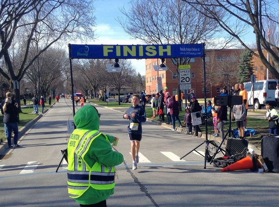 A student crosses the finish line during the 1-mile run/walk of the GetBurbed Challenge Saturday in Arlington Heights.