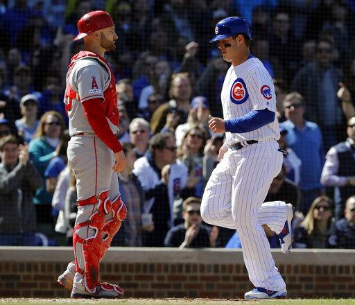 Chicago Cubs' Anthony Rizzo, right, scores on a one-run double by Javier Baez as Los Angeles Angels catcher Jonathan Lucroy looks to the field during the fifth inning of a baseball game Saturday, April 13, 2019, in Chicago.