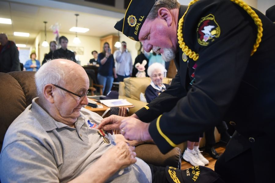 Craig Essick, commander of the American Legion Elgin Post 57, pins the World War II Victory Medal on veteran Eugene Termini during a ceremony Sunday. Termini, who lives at the Vines Senior Homes in Elgin, had been waiting for 73 years to receive the medals he earned for his service.