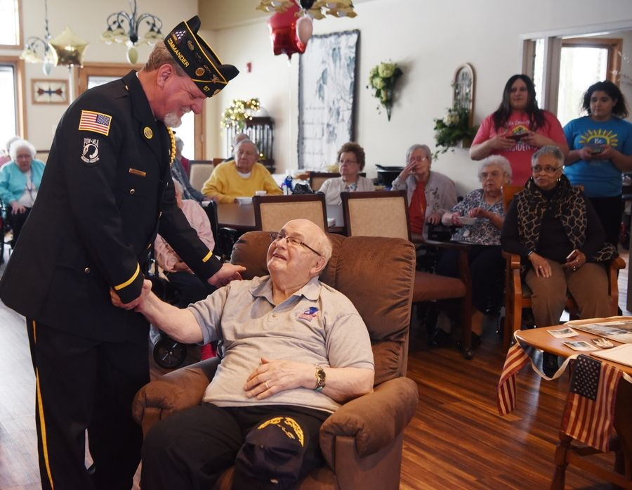 Eugene Termini, seated, a World War II veteran living at the Vines Senior Homes in Elgin, is greeted by Craig Essick, commander of the American Legion Elgin Post 57, before receiving the medals he earned during the war.