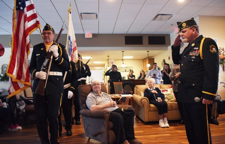 Coast Guard veteran Eugene Termini watches as members of American Legion Elgin Post 57 carry the colors during a ceremony Sunday at the Vines Senior Homes in Elgin. After waiting 73 years, Termini received the medals he earned for his service during World War II.