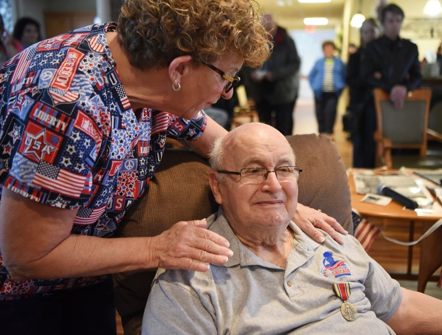 Cathy Vaden of the Vines Senior Homes in Elgin congratulates resident Eugene Termini, a World War II veteran, on Sunday after he received the medals he earned for his service.