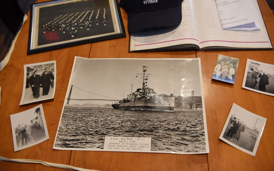 Photos and mementos from Eugene Termini's service during World War II are displayed on a table at the Vines Senior Homes in Elgin.