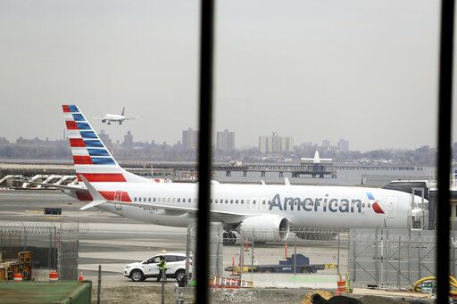 FILE - In a March 13, 2019 file photo, an American Airlines Boeing 737 MAX 8 sits at a boarding gate at LaGuardia Airport in New York. American Airlines is canceling 115 flights per day through mid-August because of ongoing problems with the Boeing 737 Max aircraft.
