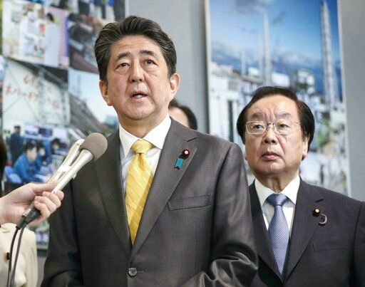 Japanese Prime Minister Shinzo Abe speaks to the media after Abe visited Fukushima Dai-ichi nuclear power plant in Okuma, Fukushima prefecture, Japan, Sunday, April 14, 2019. Prime Minister Abe inspected the reconstruction effort following the tsunami, quake and nuclear accident in 2011. (Kyodo News via AP)