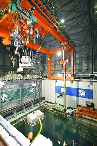 The cooling pool is seen at bottom before fuel units are removed at the Unit 3 of Fukushima Dai-ichi nuclear plant, in Okuma, Fukushima Prefecture, northeastern Japan Monday. April 15, 2019. The operator of the tsunami-wrecked nuclear plant has begun removing fuel from a cooling pool at one of three reactors that melted down in the 2011 disaster, a milestone in the decades-long process to decommission the plant. The work is carried out remotely from a control room about 500 meters (yards) away because of still-high radiation levels inside the reactor building that houses the pool. (Kyodo News via AP)