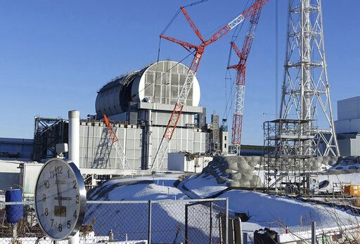 FILE - In this Jan. 25, 2018, file photo, an installation of a dome-shaped rooftop cover housing key equipment is near completion at Unit 3 reactor of the Fukushima Dai-ich nuclear power plant ahead of a fuel removal from its storage pool in Okuma, Fukushima Prefecture, northeast Japan. Tokyo Electric Power Co. said Monday, April 18, 2019, workers started removing the first of 566 fuel units stored in the pool at Unit 3. The fuel units in the pool are not enclosed and their removal to safer ground is crucial to avoid disaster in case of another major quake.