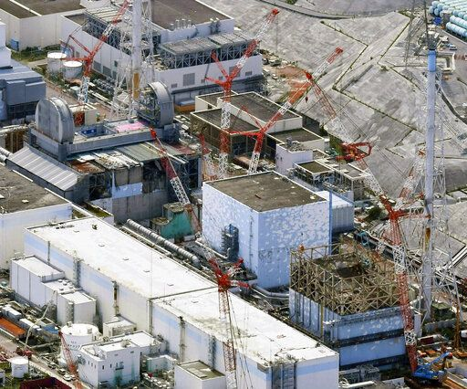 FILE - This Sept. 4, 2017 aerial file photo shows Fukushima Dai-ichi nuclear power plant reactors, from bottom at right, Unit 1, Unit 2 and Unit 3, in Okuma, Fukushima Prefecture, northeastern Japan. The operator of the wrecked Fukushima nuclear plant for the first time is removing fuel from a cooling pool at one of three reactors that melted down in the 2011 disaster, a milestone in the decades-long process to decommission the plant. Tokyo Electric Power Co. said Monday, April 15, 2019, workers started removing the first of 566 fuel units stored in the pool at Unit 3. The fuel units in the pool are not enclosed and their removal to safer ground is crucial to avoid disaster in case of another major quake.(Daisuke Suzuki/Kyodo News via AP, File)