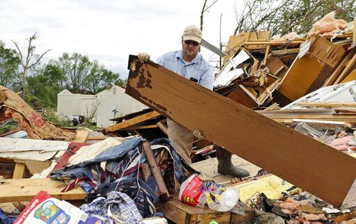 Roman Brown moves part of a wall out of his way as he looks for a friends medicine in their destroyed home along Seely Drive outside of Hamilton, Miss. after a storm moved through the area on Sunday, April 14, 2019.