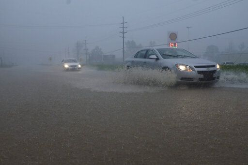 Vehicles travel through a flooded section of Highway 61 South following severe weather on Saturday, April 13, 2019 in Vicksburg, Miss. Authorities say a possible tornado has touched down in western Mississippi, causing damage to several businesses and vehicles. John Moore, a forecaster with the National Weather Service in Jackson, says a twister was reported Saturday in the Vicksburg area of Mississippi and was indicated on radar. (Courtland Wells/The Vicksburg Post via AP)