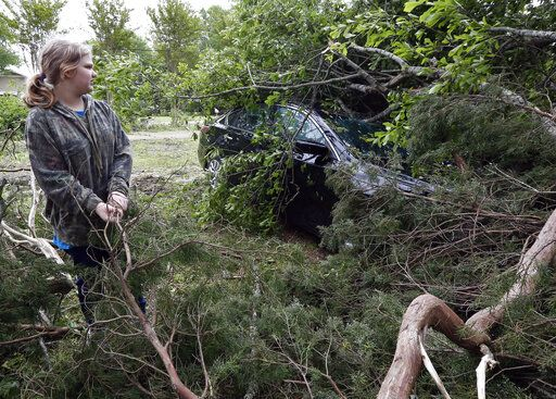 Kayla Easterling of Flora, Miss., looks at a tree-limbed covered automobile that belongs of a member of her church, Sunday, April 14, 2019. The vehicle was one of several properties damaged or destroyed by Saturday's severe weather. The storm was one of several that hit the state.