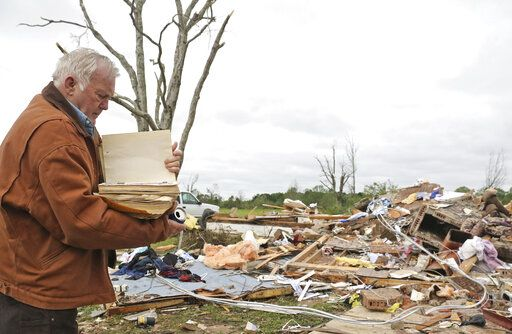Robert Scott looks through a family Bible that he pulled out of the rubble Sunday, April 14, 2019, from his Seely Drive home outside of Hamilton, Miss., after an apparent tornado touched down Saturday night.