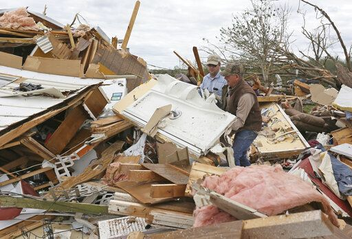 Roman Brown, left and Sam Crawford, right move part of a shower wall out of their way as they help a friend look for their medicine in their destroyed home Sunday, April 14, 2019, along Seely Drive outside of Hamilton, Miss. after an apparent tornado touched down Saturday, April, 13, 2019.