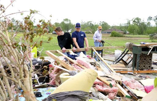 Riley Carter, left and Thomas Boles, center help Jerry Whitaker, right clean up the remains of his brothers house on Seely Drive outside of Hamilton, Miss. after a storm moved through the area on Sunday, April 14, 2019.