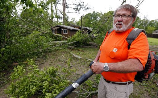 David Poole of Flora, Miss., recalls seeing the falling debris from Saturday's storm as he begins clean up Sunday, April 14, 2019. Poole, 63, said he spent much of the evening outside his home with a broom, sweeping away flash flood waters from the intense rain. The storm was one of several that hit the state.