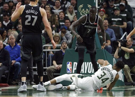 Milwaukee Bucks' Giannis Antetokounmpo (34) falls to the floor after being fouled by Detroit Pistons' Thon Maker (7) during the first half of Game 1 of an NBA basketball first-round playoff series Sunday, April 14, 2019, in Milwaukee.