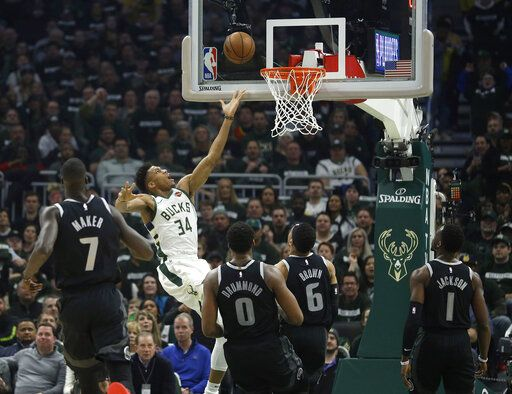 Milwaukee Bucks' Giannis Antetokounmpo (34) shoots against multiple Detroit Pistons defenders during the first half of Game 1 of an NBA basketball first-round playoff series Sunday, April 14, 2019, in Milwaukee.