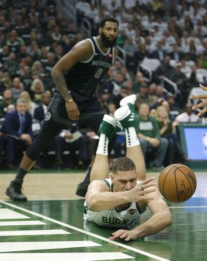 Milwaukee Bucks' Brook Lopez is unable to save the ball from going out of bounds in front of Detroit Pistons' Andre Drummond during the first half of Game 1 of an NBA basketball first-round playoff series Sunday, April 14, 2019, in Milwaukee.