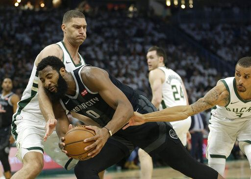 Detroit Pistons' Andre Drummond (0) is fouled as he drives between Milwaukee Bucks' Brook Lopez and George Hill during the first half of Game 1 of an NBA basketball first-round playoff series Sunday, April 14, 2019, in Milwaukee.