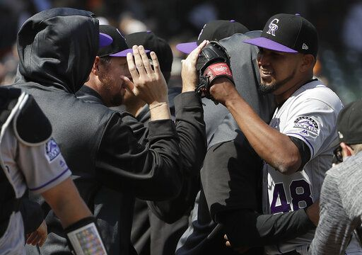 Colorado Rockies pitcher German Marquez, right, celebrates with teammates after they defeated the San Francisco Giants in a baseball game in San Francisco, Sunday, April 14, 2019.