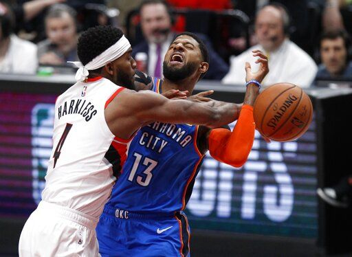 Portland Trail Blazers forward Maurice Harkless, left, knocks the ball away from Oklahoma City Thunder forward Paul George, right, during the first half of Game 1 of a first-round NBA basketball playoff series in Portland, Ore., Sunday, April 14, 2019.